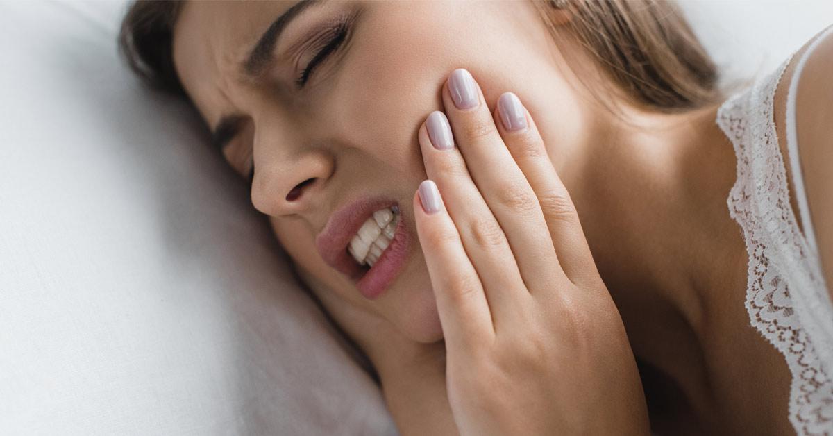 Mujer con cara de dolor con las manos tocando la mandíbula y apretando los dientes. Esta imagen se utiliza para ilustrar una entrada sobre qué es el bruxismo.