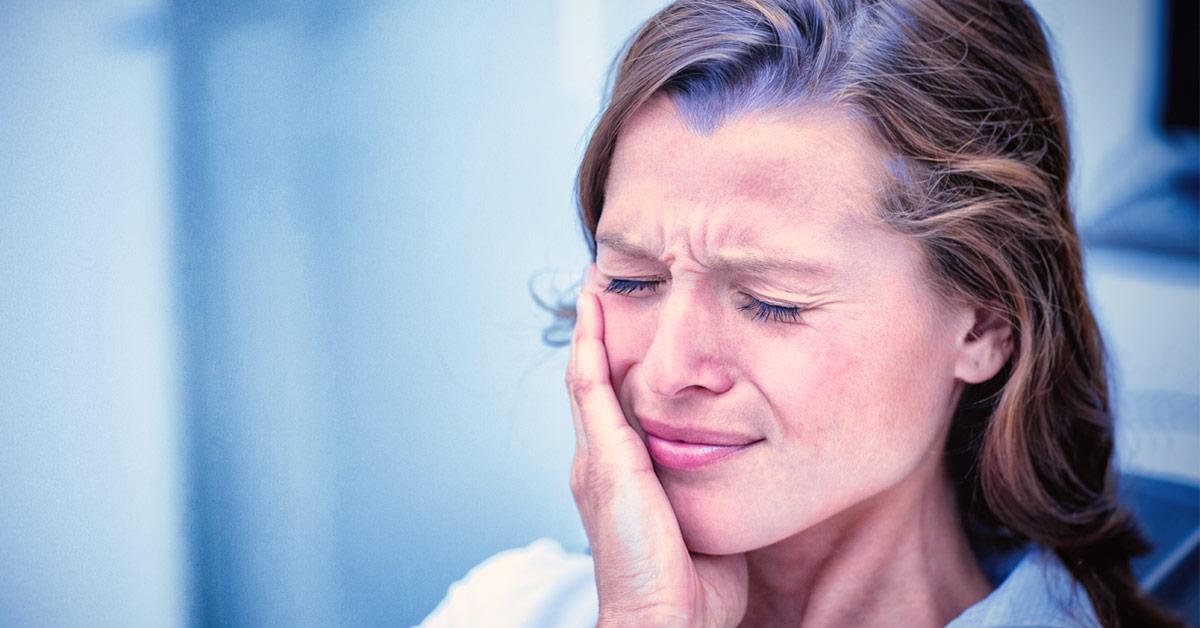 Mujer tocándose la mejilla con cara de dolor, como refiriendo un dolor de muelas. Esta imagen se utiliza para ilustrar una entrada sobre cómo aliviar y quitar el dolor de muelas.
