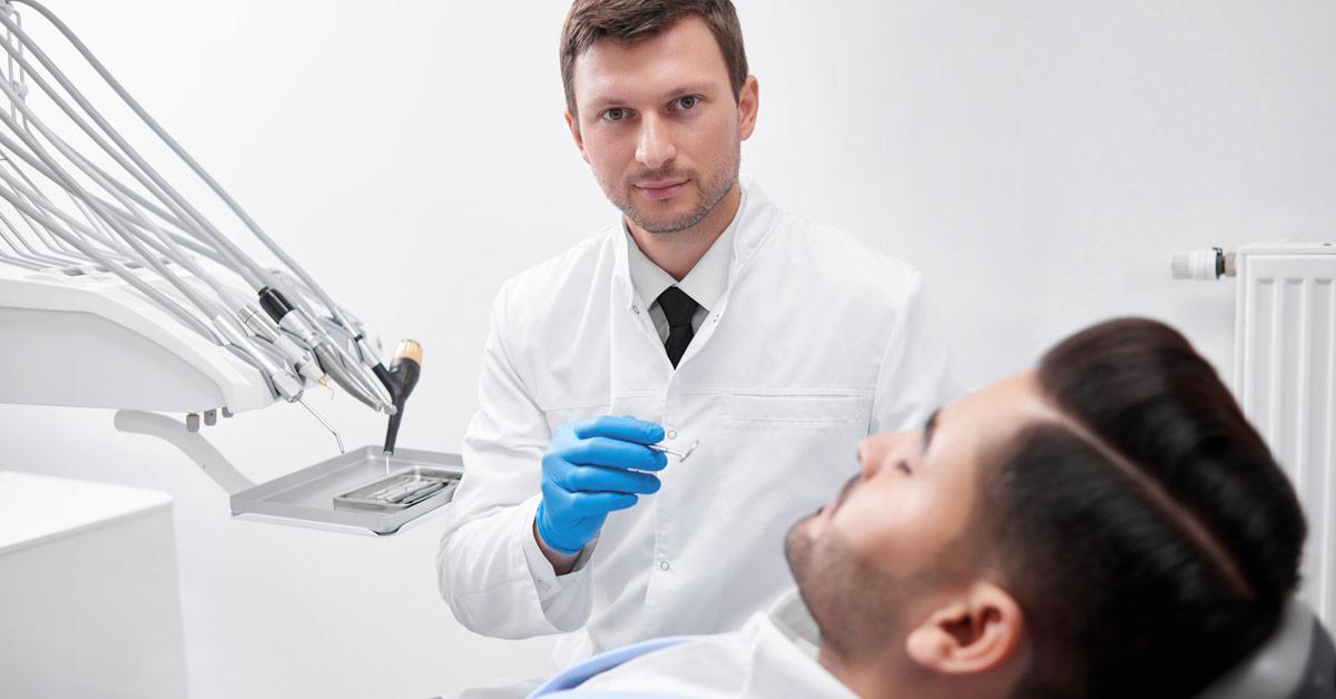 Dentista en la consulta sosteniendo un espejo dental frente a un paciente acostado en el sillón.