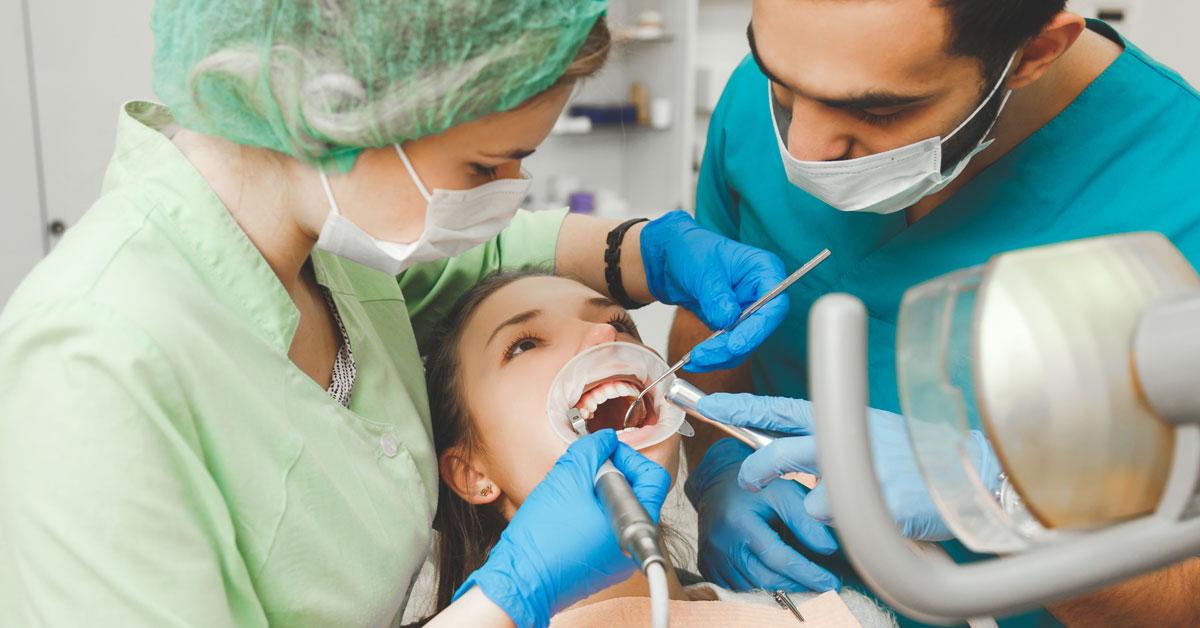 Mujer y hombre sanitarios realizándole una limpieza dental a una mujer.